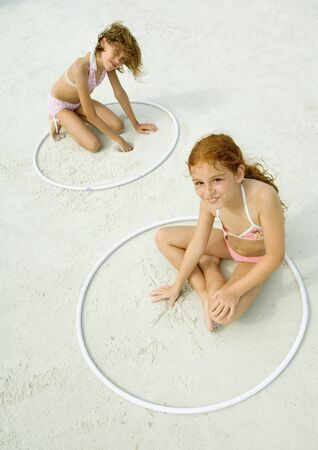 Girls sitting in rings, playing in sand on beach