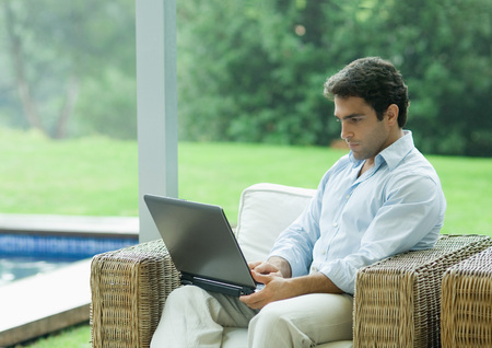 Man using laptop outdoors in armchair