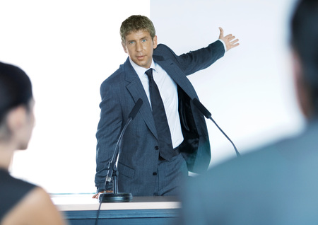persuading: Speaker standing next to microphones during seminar LANG_EVOIMAGES