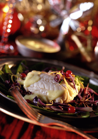 Piece of cod with red cabbage and dressing on plate, close-up