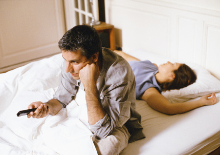 Man sitting up in bed, pointing remote control, woman lying behind him