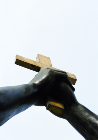 Statue, hands holding crucifix, low angle view