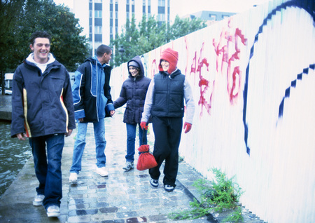 Four young people walking on sidewalk next to graffiti-covered wall