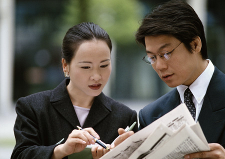 Businessman, businesswoman together looking at newspaper