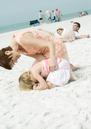 Family at the beach, mother bending over daughter curled up on sand LANG_EVOIMAGES