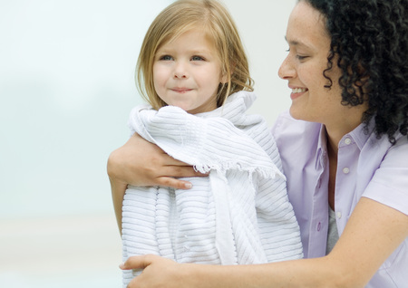Woman holding daughter wrapped in a towel