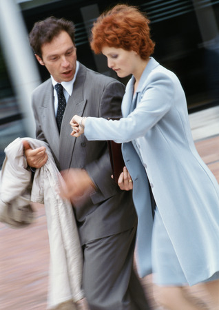 Businessman and businesswoman walking side by side outside, businesswoman looking at watch LANG_EVOIMAGES