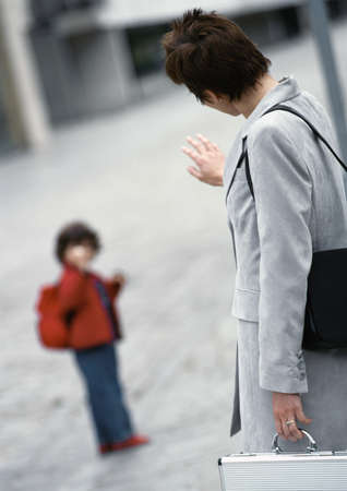 mid morning: Businesswoman waving to child