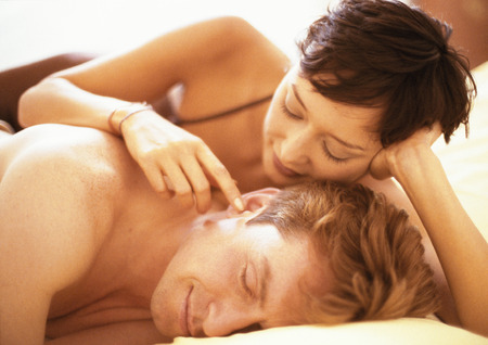 Couple lying in bed, woman touching mans ear