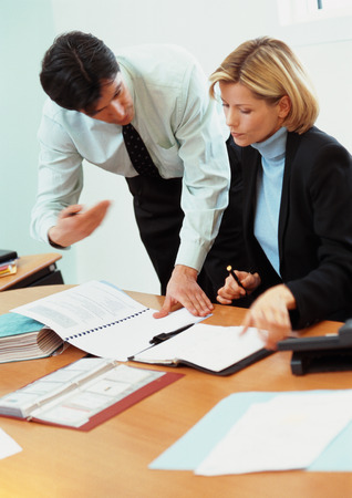 Businessman and businesswoman looking at documents on desk