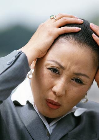 Businesswoman, hands on head, portrait LANG_EVOIMAGES