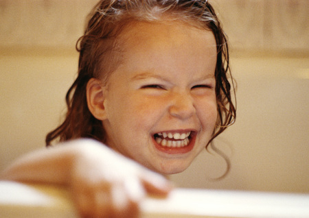 Girl with wet hair holding edge of bathtub, smiling LANG_EVOIMAGES