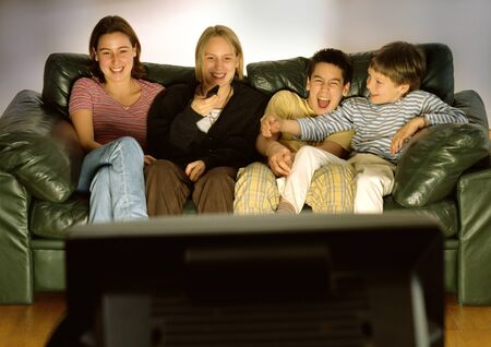 Three young people and one child sitting on green couch together, laughing, blurred rear view of tv in foreground LANG_EVOIMAGES