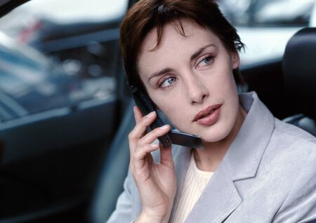 distractions: Businesswoman in car using cell phone, looking away, portrait LANG_EVOIMAGES