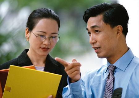 Businessman, businesswoman side by side, woman holding folders, head and shoulders LANG_EVOIMAGES