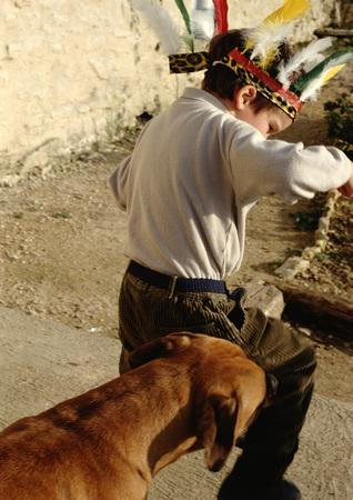 headress: Boy wearing feather headress, followed by dog, rear view