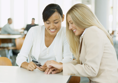 Two young business women looking at cell phone together