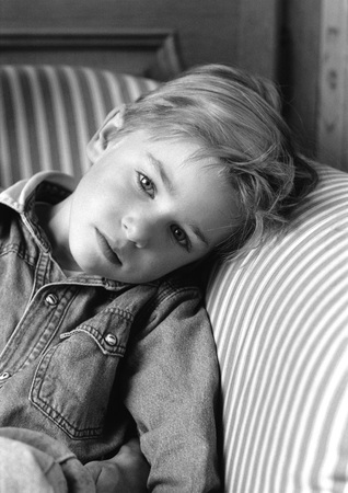 Young boy leaning head on chair arm, black and white portrait LANG_EVOIMAGES