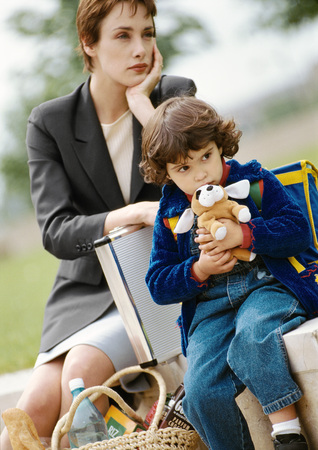 Businesswoman and child sitting, child hugging stuffed dog LANG_EVOIMAGES