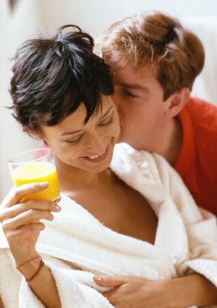 smooching: Man kissing woman from behind, woman holding glass of juice, head and shoulders, close-up