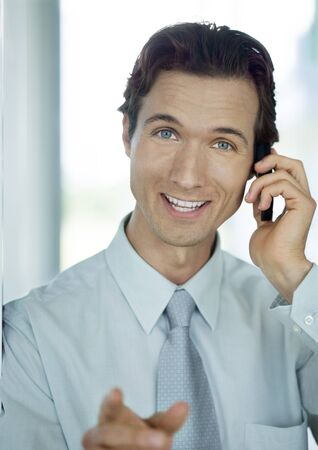 Businessman phoning and smiling