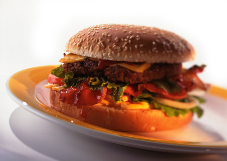 carnes y verduras: Cheeseburger with tomatoes, lettuce, and bacon on sesame seed bun, close-up LANG_EVOIMAGES