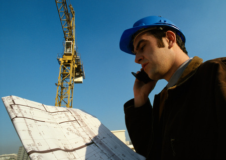 Man wearing hard hat, holding cell phone and blueprints