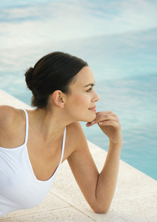 Woman leaning on elbow near edge of pool