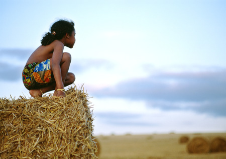 Girl crouching on haystack, side view LANG_EVOIMAGES