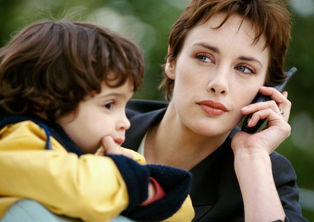 Businesswoman on cell phone with child, close-up