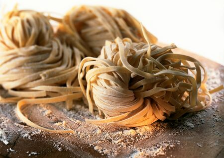 Mounds of fresh pasta on floured board, close-up