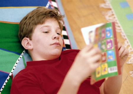 Boy reading in bed LANG_EVOIMAGES