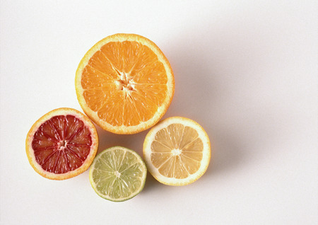 Cross sections of orange, blood orange, lemon, lime, close-up, high angle view, white background