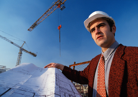 Man wearing hard hat, holding blueprint, cranes in background, low angle view LANG_EVOIMAGES