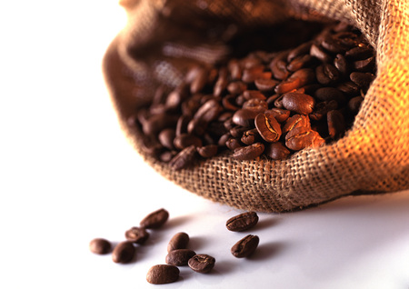 Coffee beans spilling out of burlap sack