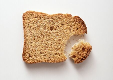 Slice of bread with piece broken off, close-up LANG_EVOIMAGES