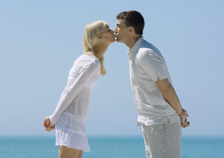 smooching: Couple leaning forward, kissing, sea in background LANG_EVOIMAGES