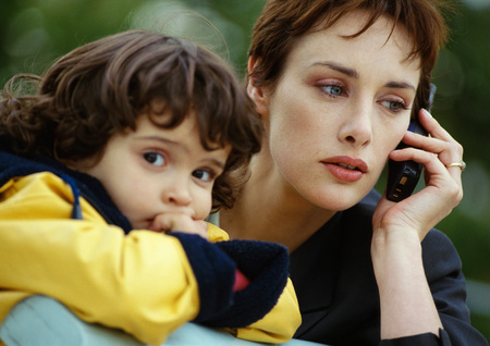 Businesswoman on cell phone next to child, close-up