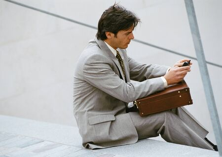 joblessness: Businessman sitting on stairs, looking at cell phone