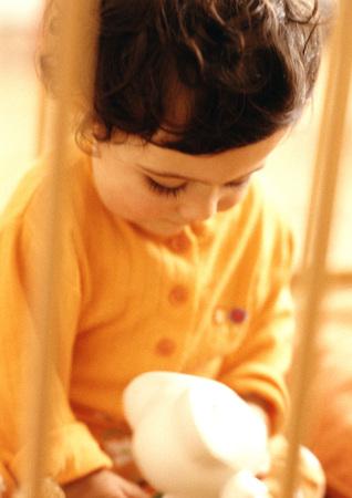 pyjama: Young child looking at stuffed animal, warm toned, blurry