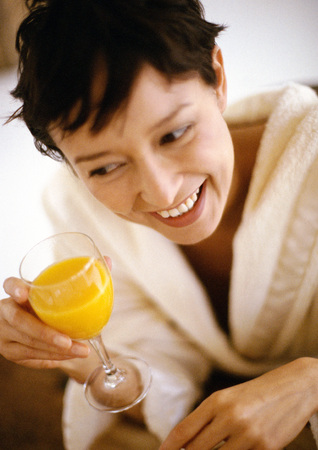 Woman holding glass of juice, smiling, high angle view, close-up