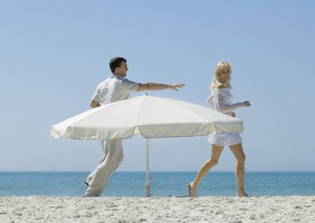 Man chasing woman around parasol on beach LANG_EVOIMAGES