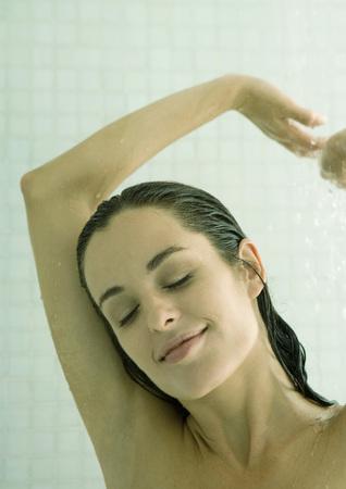 mujer bañandose: Mujer tomando la ducha, los brazos arriba y los ojos cerrados LANG_EVOIMAGES