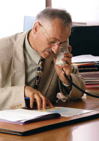 Man looking at documents while using phone