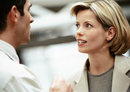 Businessman and businesswoman face to face, looking at each other, close-up LANG_EVOIMAGES