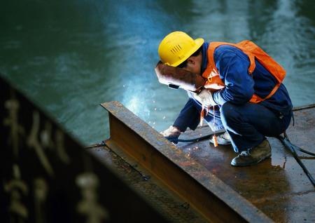 Welder wearing welding mask, crouching and welding girder