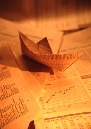 Paper boat made from financial documents, close-up