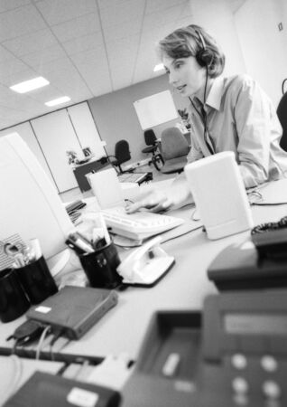 Businesswoman wearing headset in office, side view, B&W LANG_EVOIMAGES