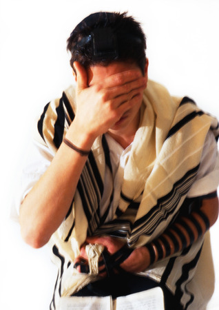 Jewish man wearing Tefillin and Tallith for prayer, covering face with hand, close-up LANG_EVOIMAGES