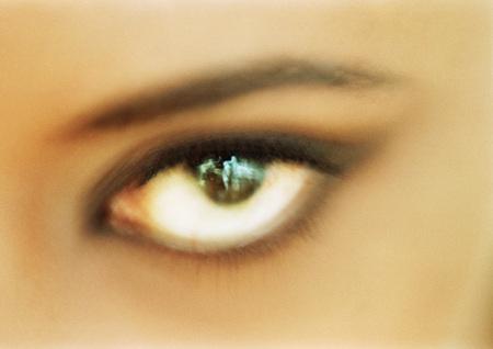 Womans brown eye looking at camera, blurred close up